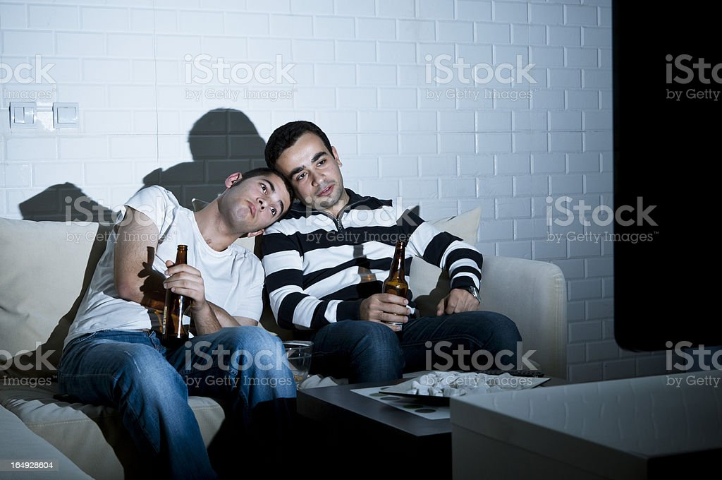 Two men watching television royalty-free stock photo