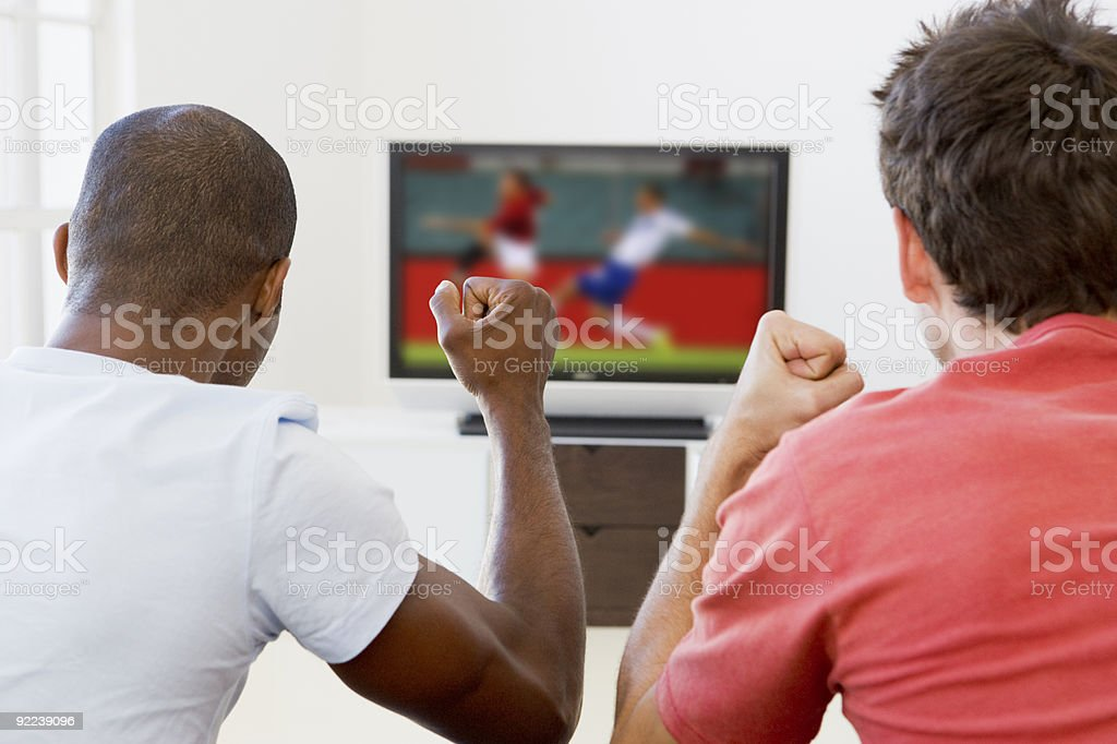 Two men watching television stock photo