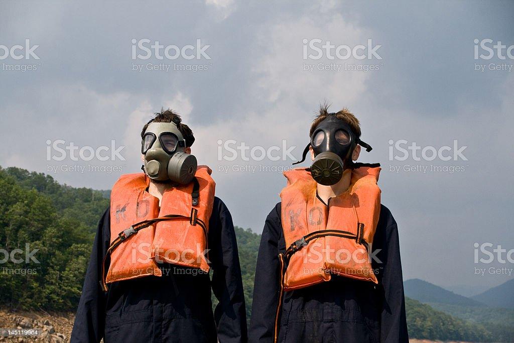 Two men wear gas masks on lake stock photo
