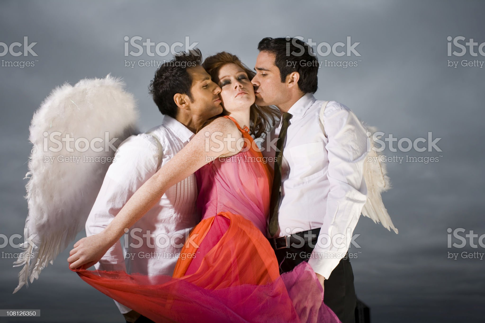 Two Men Wearing Angel Wings Kissing Young Woman royalty-free stock photo