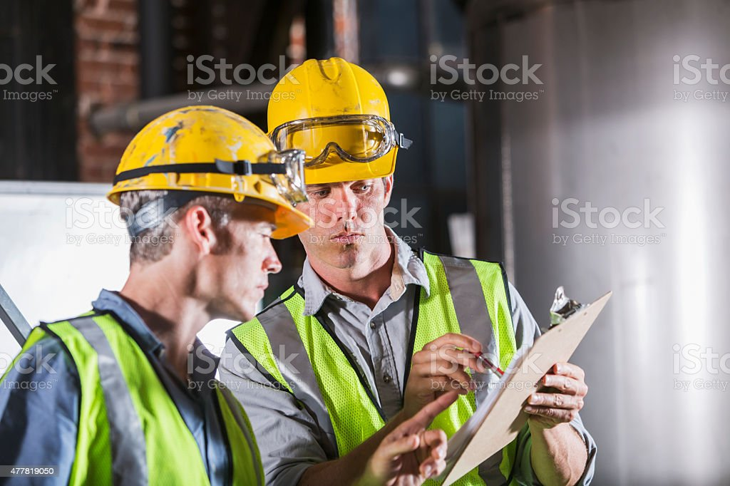 Two men wearing hardhats, vests and safety glasses stock photo