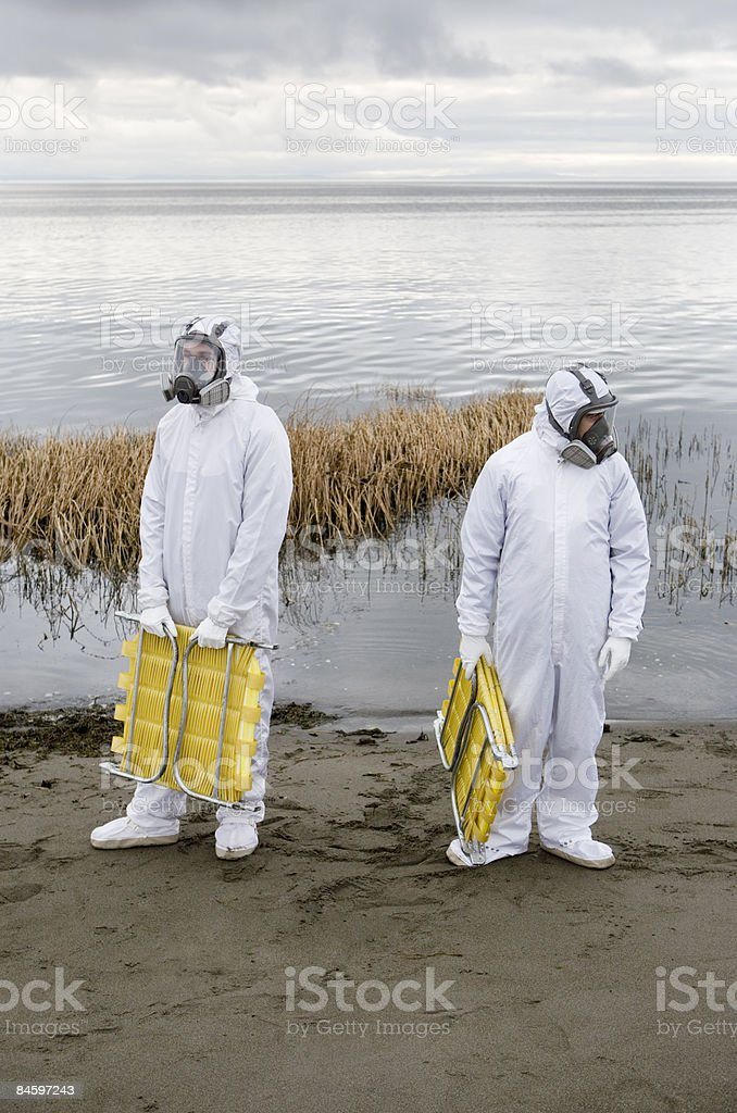 Two men wearing hazmat suits carry beach chairs stock photo