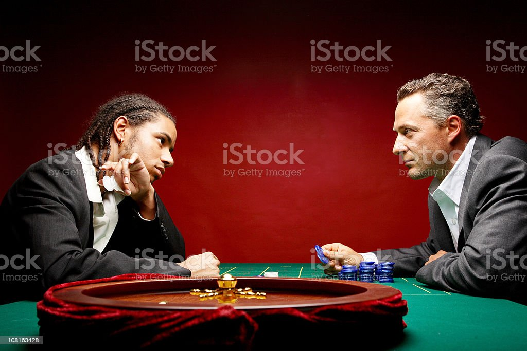 Two Men Wearing Suits and Sitting at Casino Playing Roulette royalty-free stock photo
