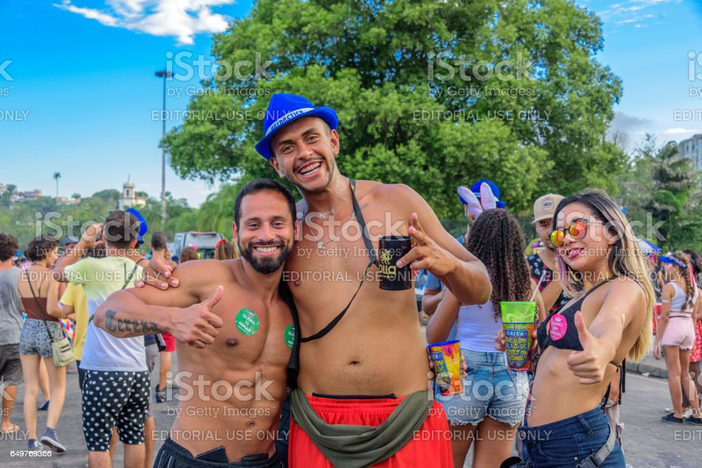 Two men with bare chest and young woman in bikini on the backround of Nossa Senhora da Gloria do Outeiro Church, Carnaval 2017 stock photo