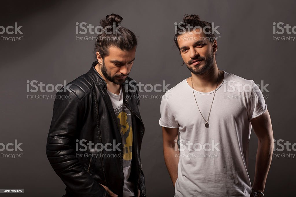 Two men with hair buns and facial hair stock photo