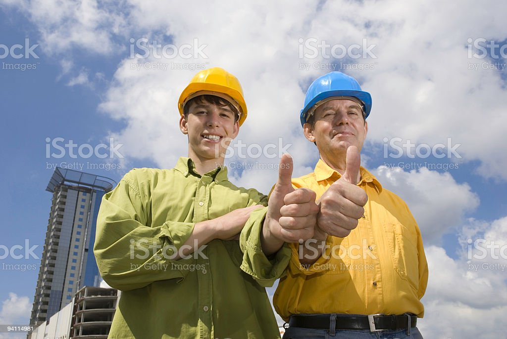 Two men with hard hats showing thumbs up royalty-free stock photo