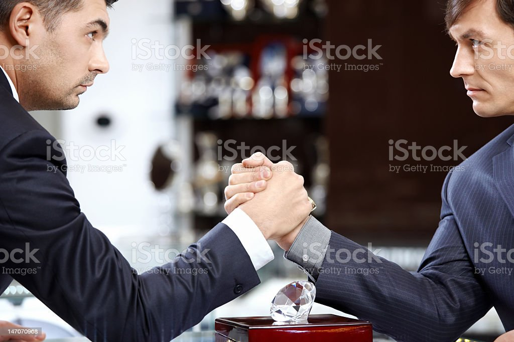 Two men with serious facial expressions arm wrestling stock photo