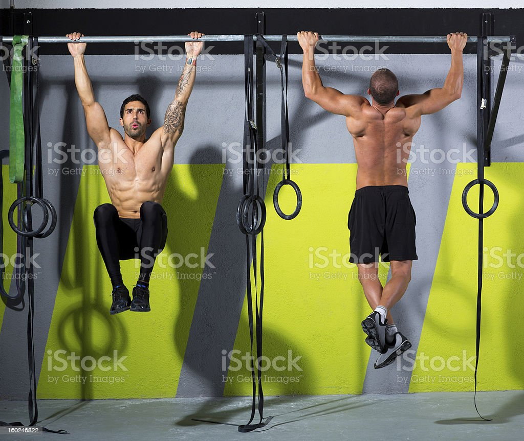 Two men work out on gym pull-up bars stock photo