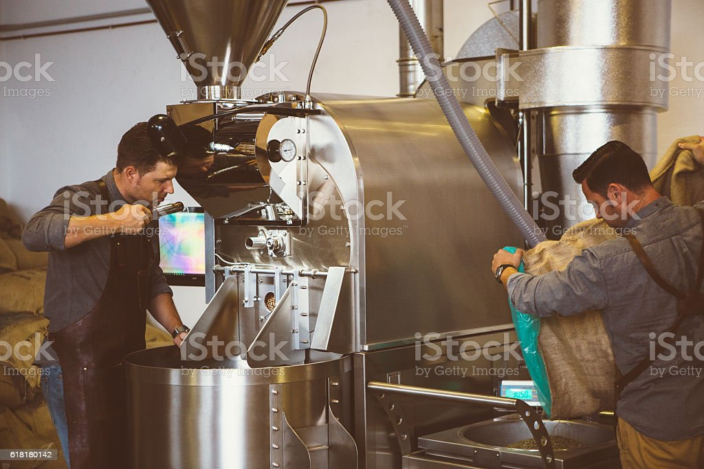 Two men working at coffee roasting factory stock photo