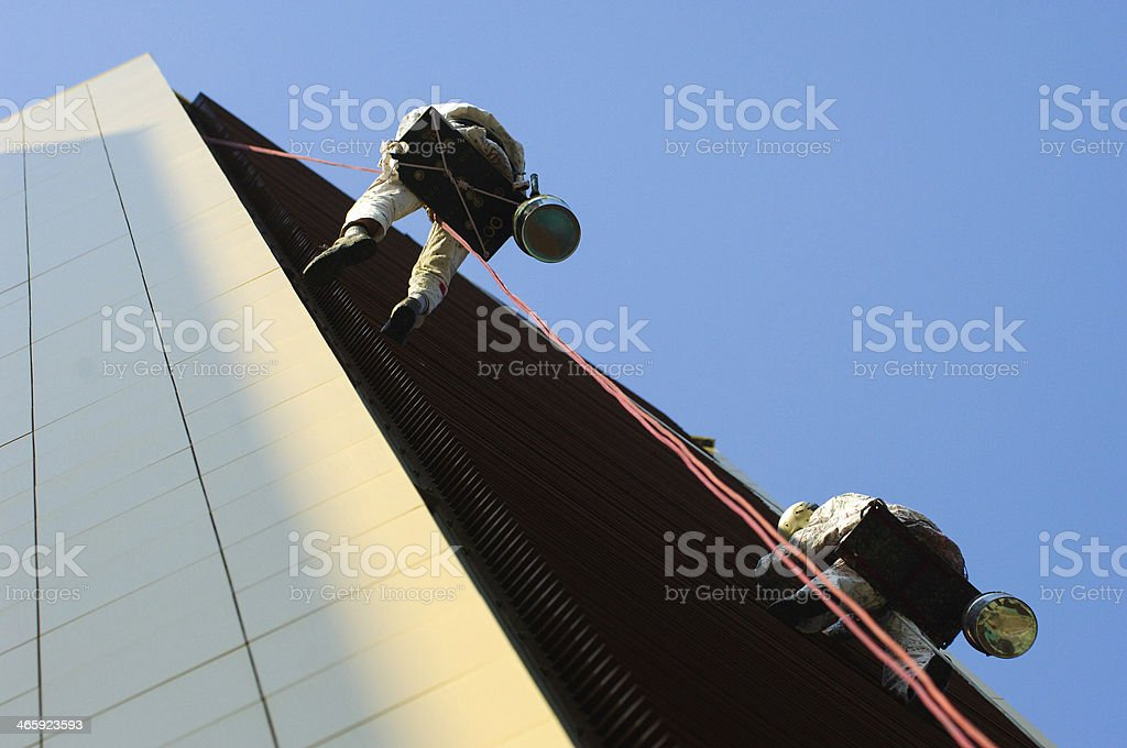 Two men working high on a building stock photo