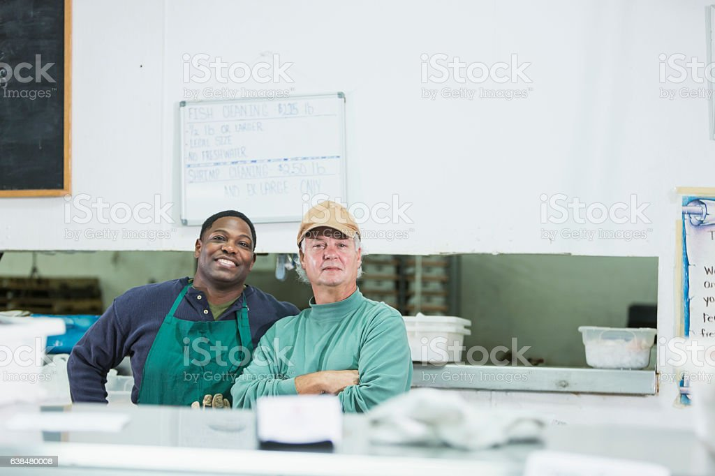 Two men working in a fish market behind display counter stock photo