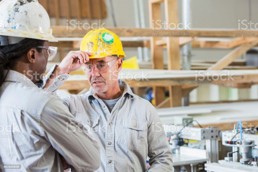 Two men working in a small factory having discussion stock photo
