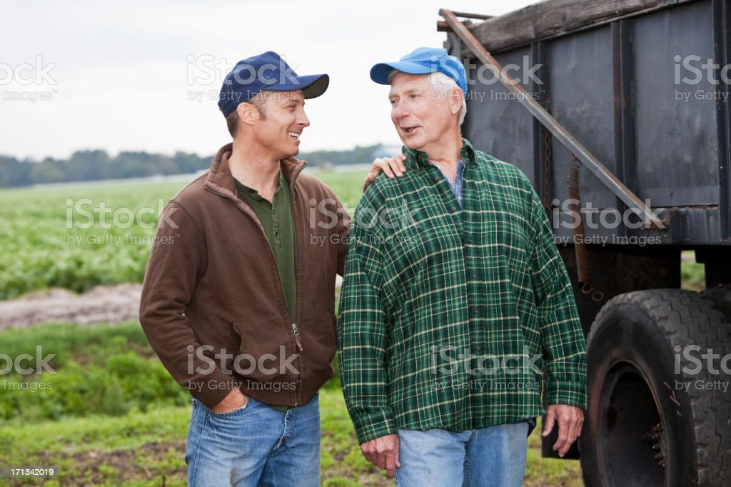 Two men working on a farm, talking by a truck stock photo