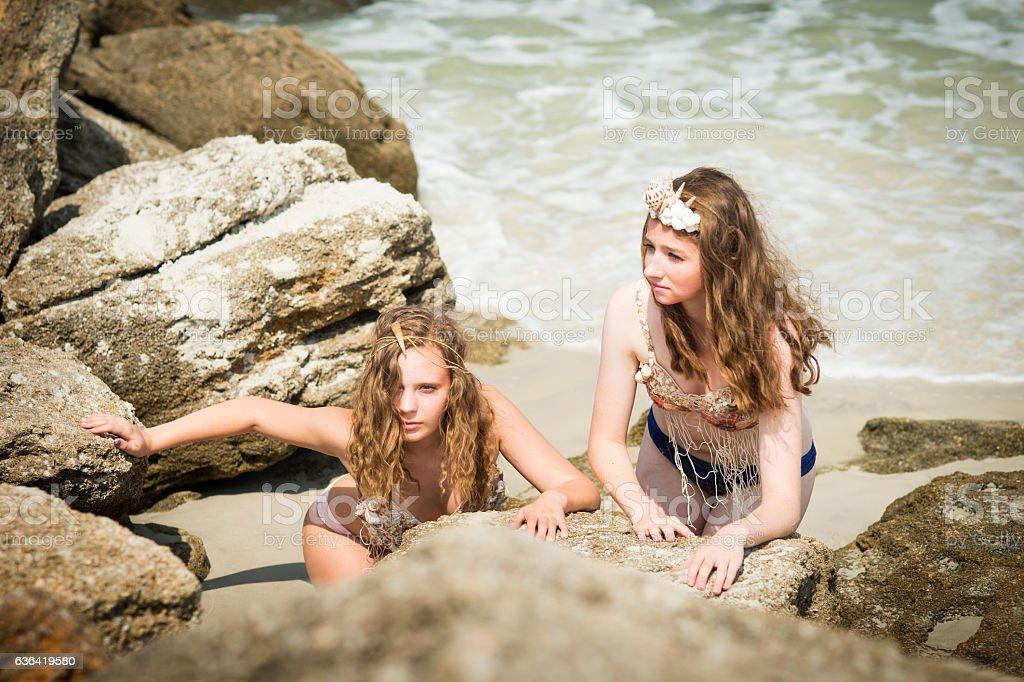 Two mermaids hiding behind coastal rocks stock photo