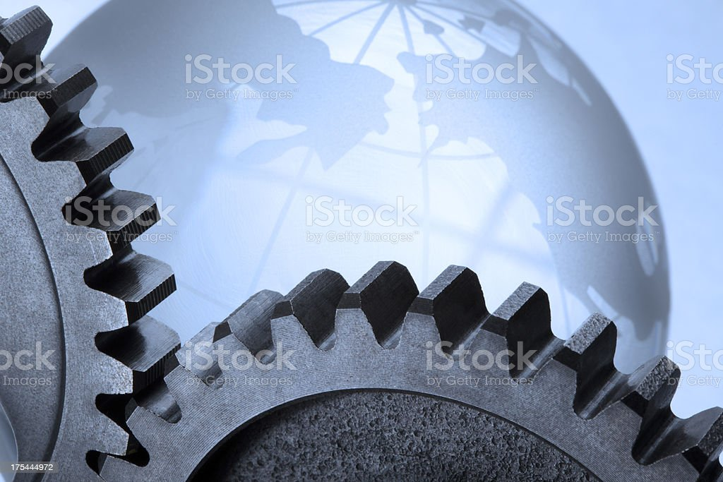 Two meshing gears in front of crystal globe stock photo