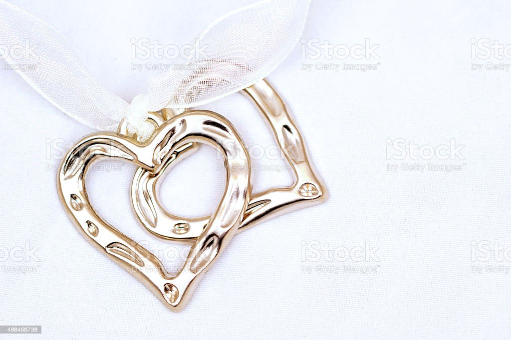 Two metal hearts on light background stock photo