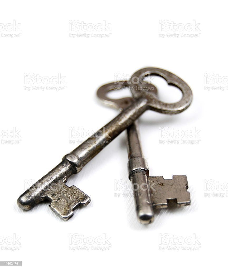Two metal keys on top of each other over a white background stock photo