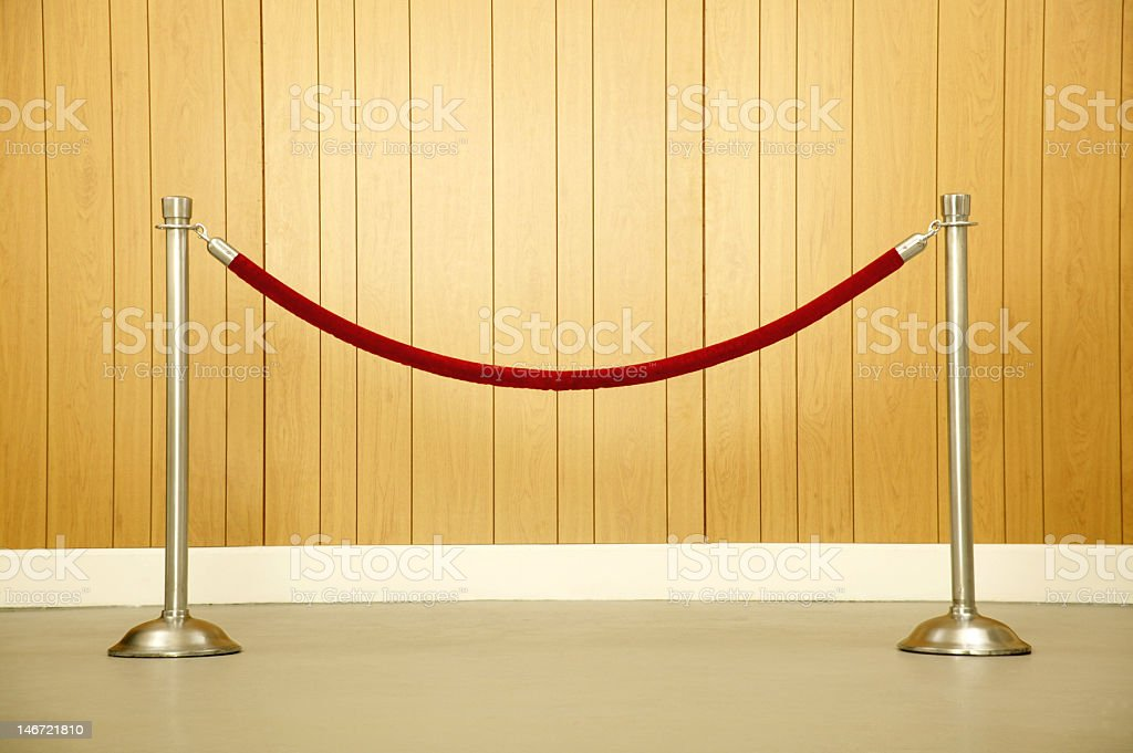 Two metal poles holding up a red velvet rope stock photo