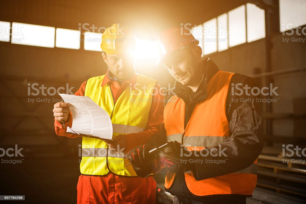 Two metal workers measuring steel with Vernier Caliper. stock photo