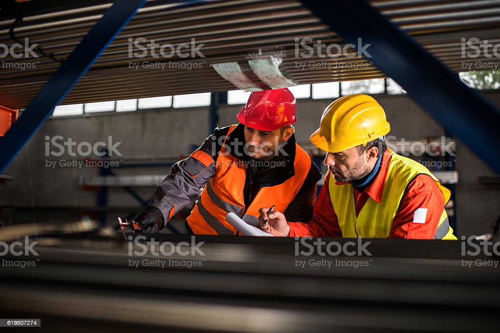 Two metal workers working together in aluminum mill. stock photo