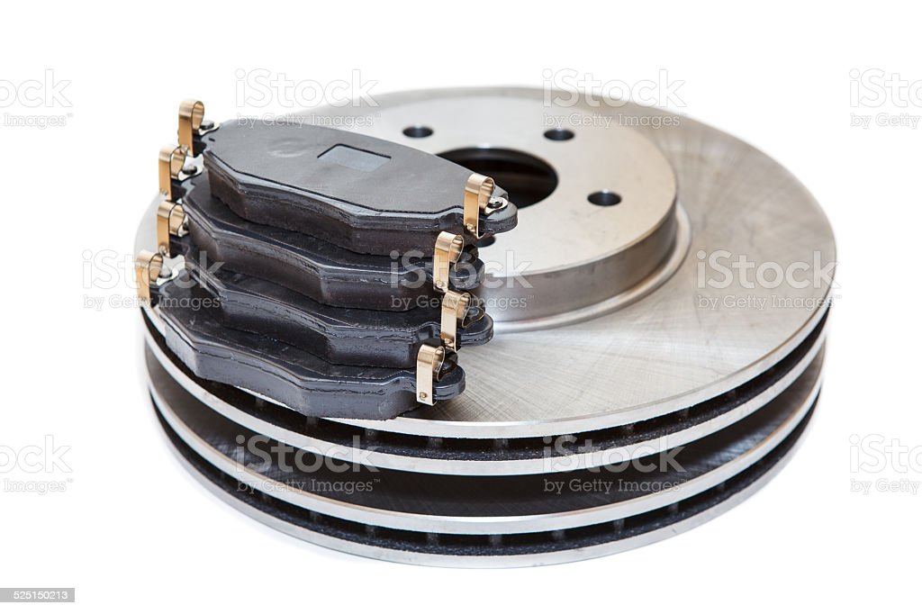 Two metallic brake disks and pads isolated on white background stock photo