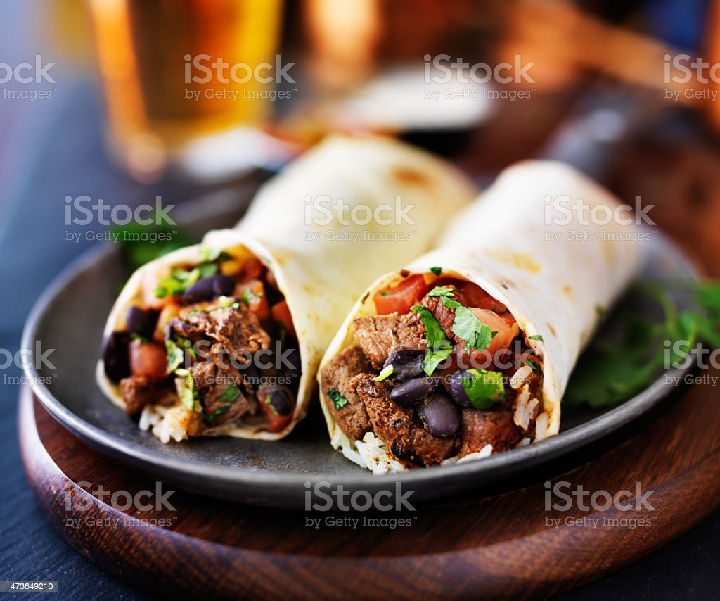 two mexican steak burritos with beer stock photo