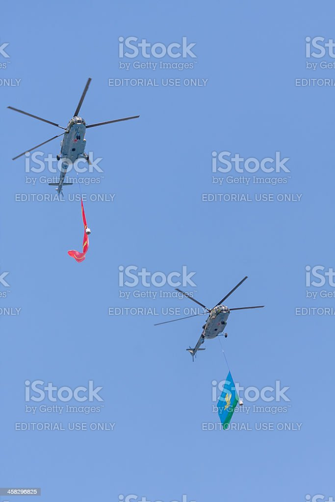 Two Mi-8 helicopters with giant flags fly against sky background royalty-free stock photo