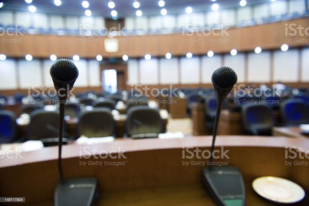 Two microphones on a podium overlooking empty seats royalty-free stock photo