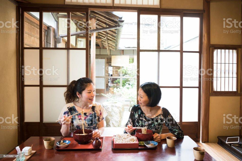 Two mid adult women sitting in Japanese restaurant eating dinner stock photo