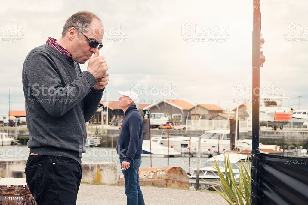 Two middle age men smoking in a small french harbour. stock photo