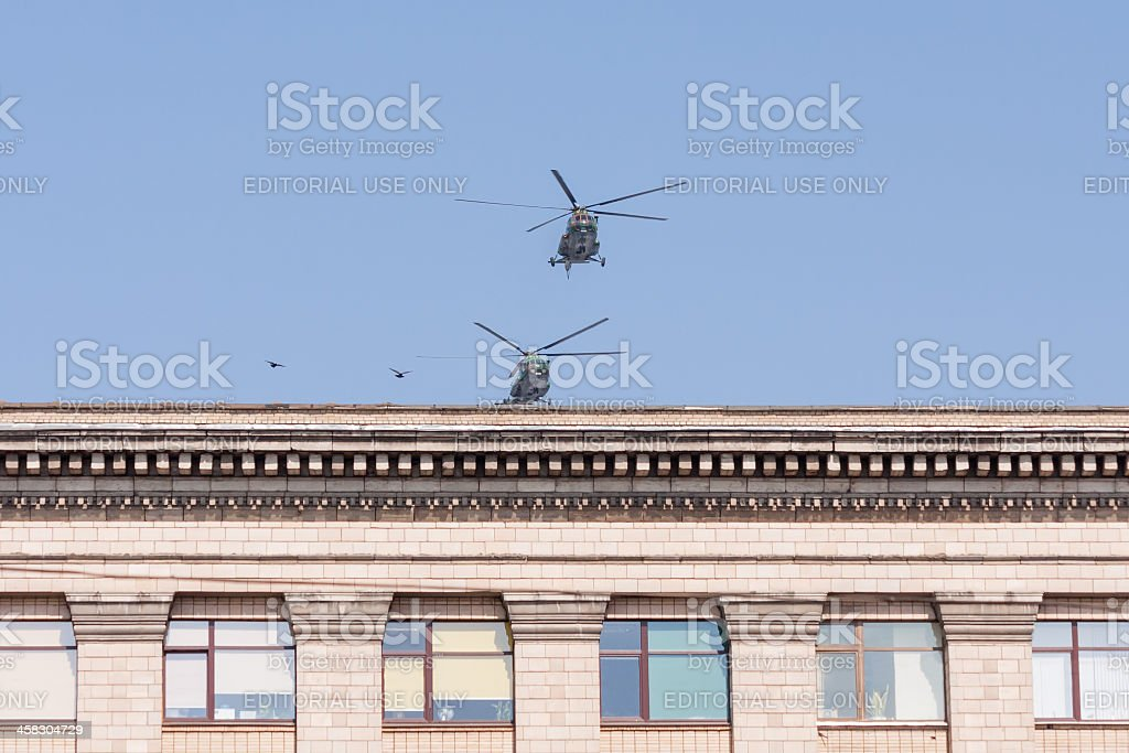 Two Mil Mi-8 (Hip) medium transport helicopters fly over building royalty-free stock photo
