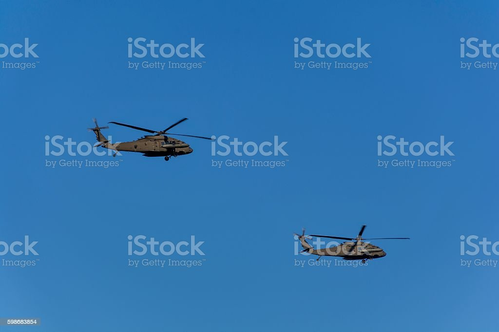 Two military helicopters flying against blue sky stock photo