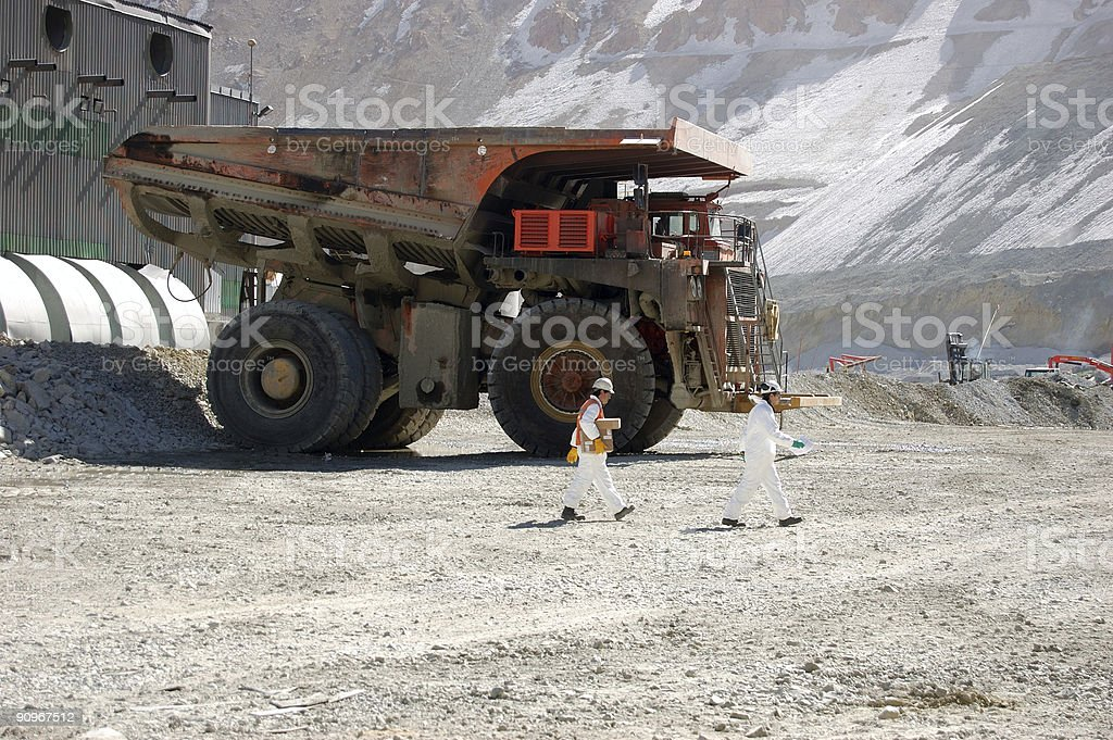 Two miners in white hard hats walk past large mining truck stock photo