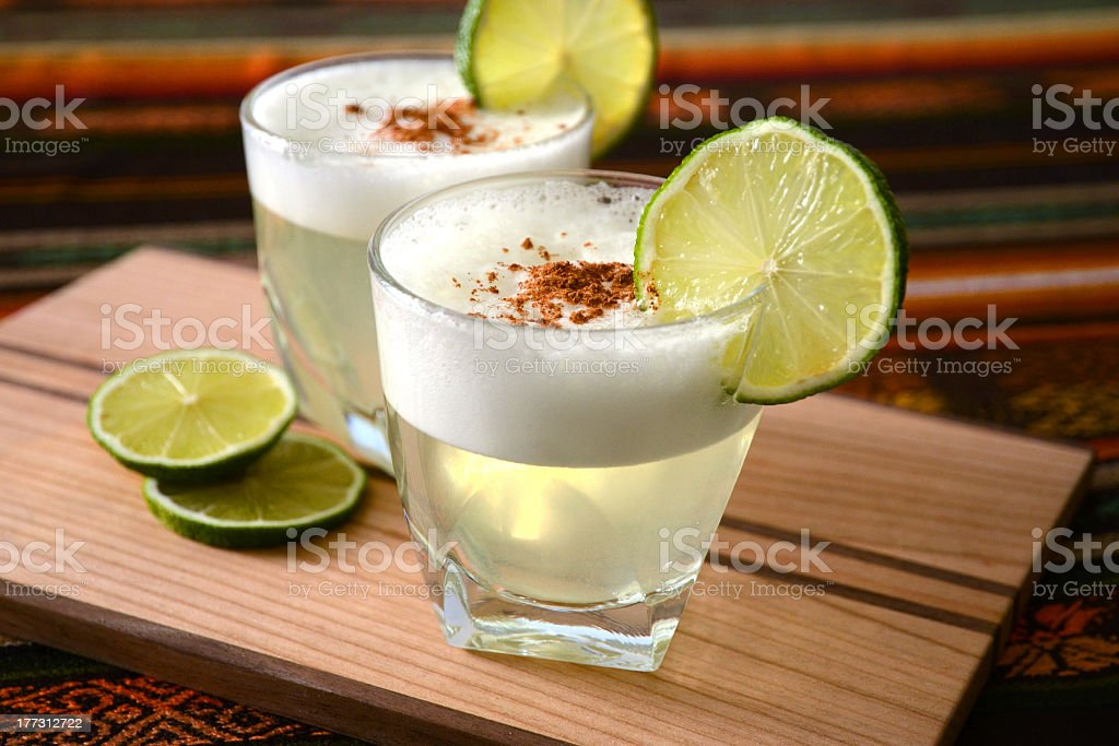 Two mini glasses of Pisco sour drinks stock photo