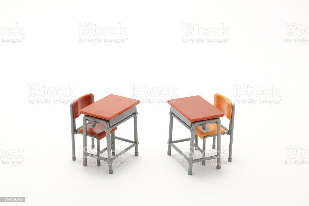Two miniature school desks on white background. stock photo