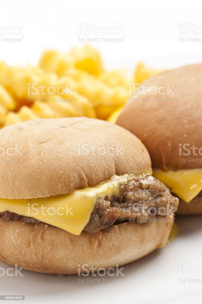 Two mini-cheeseburgers with crinkle cut French fries. stock photo