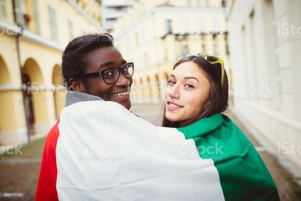 Two mixed race young women covered by Italian flag stock photo