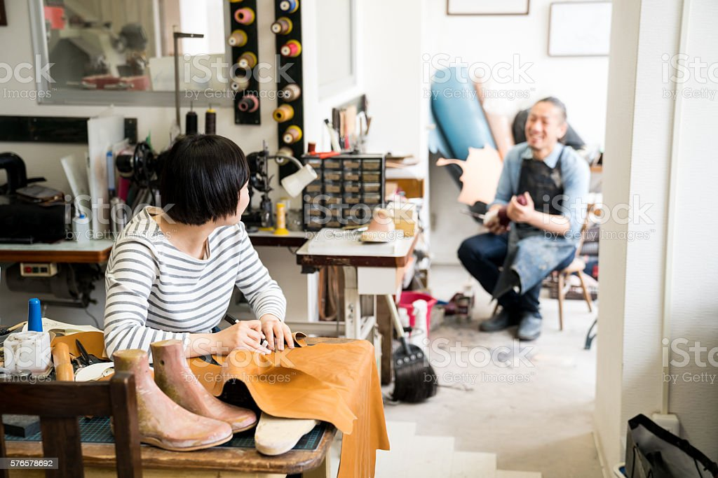 Two modern cobblers working in their small shoe shop stock photo