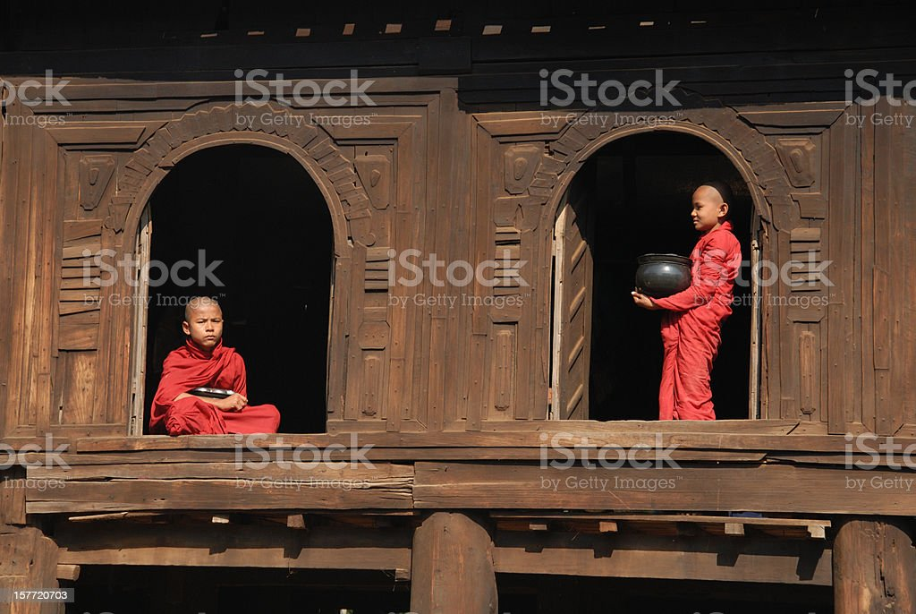 Two monks standing in 2 windows royalty-free stock photo
