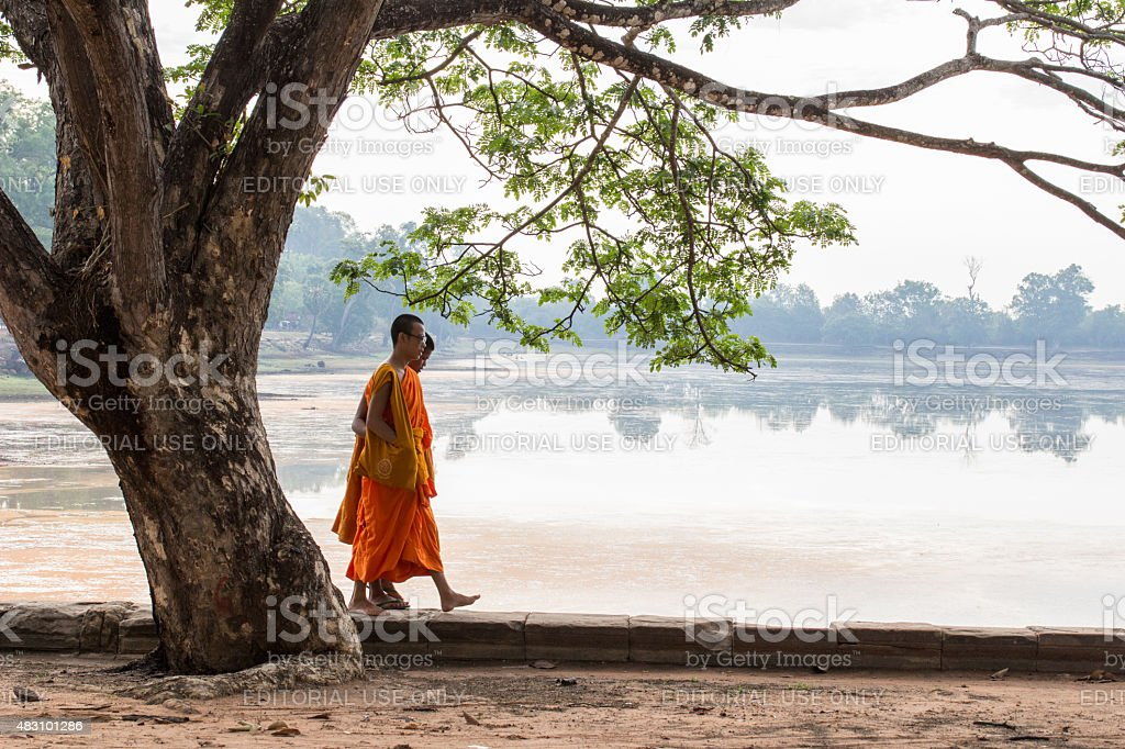 Two monks walking along the lake, Pre rup temple-Angkor-Cambodia stock photo