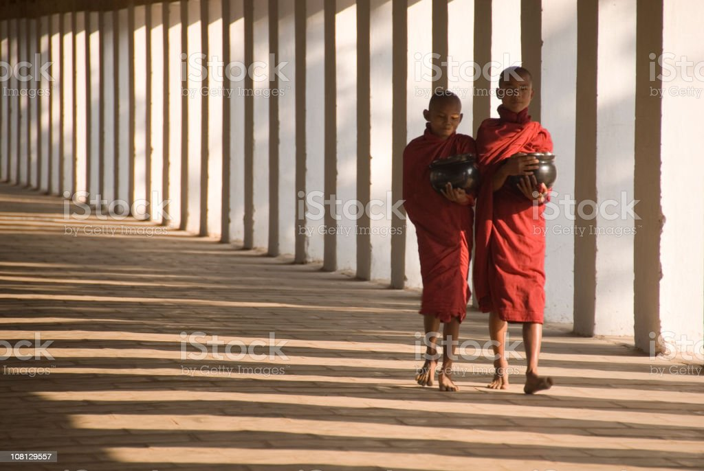 Two monks walking down a temple hallway royalty-free stock photo
