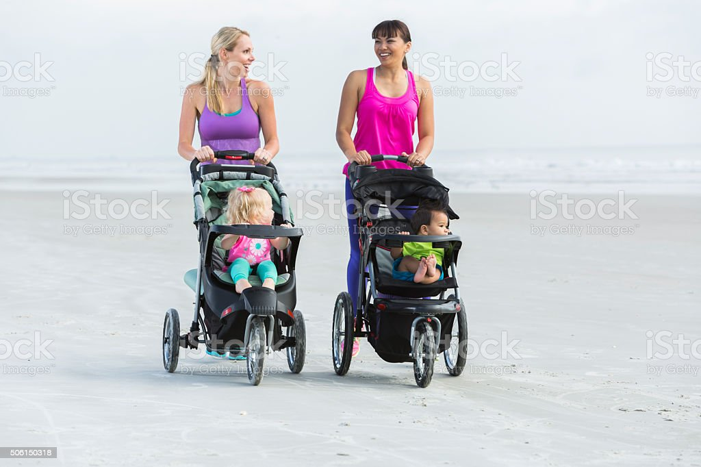 Two mothers and babies in strollers walking on beach stock photo
