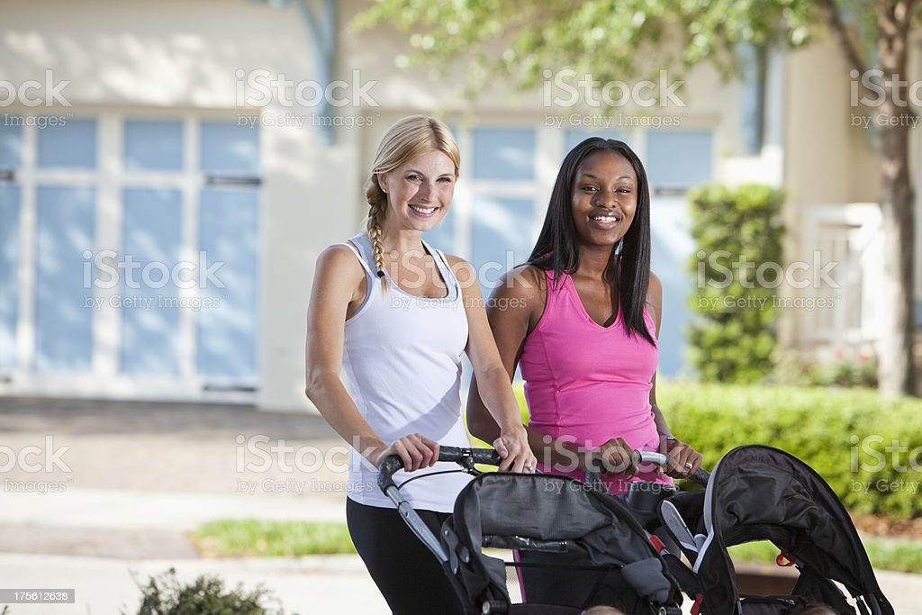 Two mothers with babies in strollers stock photo