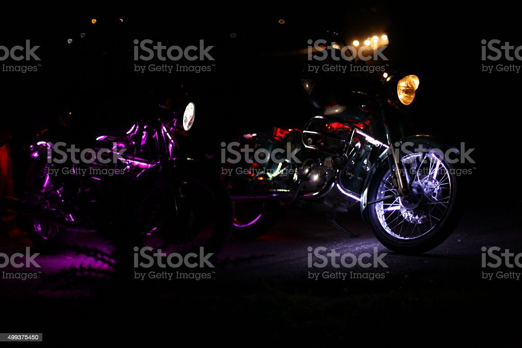 two motorcycles with illuminated at night in the mountains stock photo