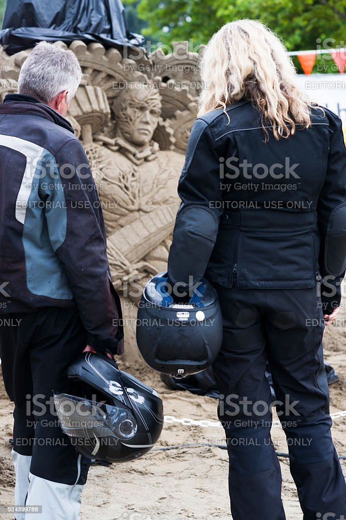 Two motorcyclists look at sand sculptures stock photo