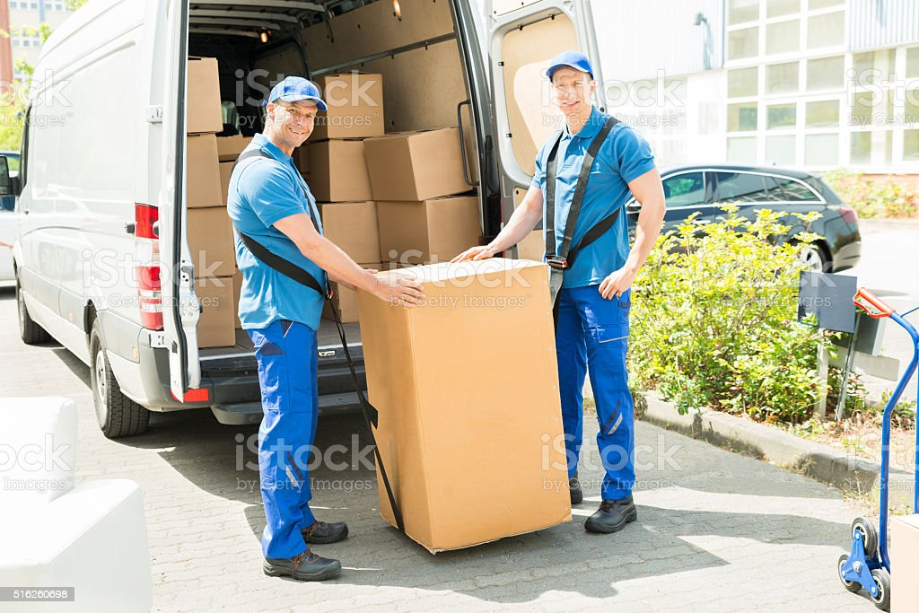 Two Movers Loading Boxes In Truck stock photo