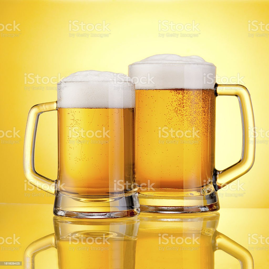 Two Mugs beer with cap of foam on yellow stock photo