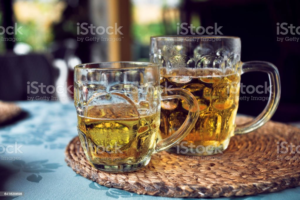 Two mugs of beer in the cozy seaside cafe stock photo