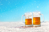 Two mugs of cold beer on the snow