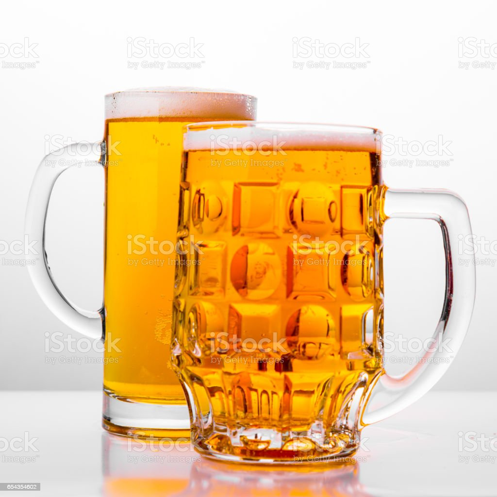 Two Mugs of fresh beer with cap foam stock photo